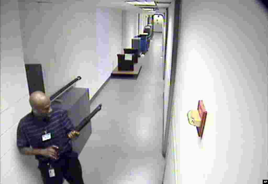 آرون الکسیس ۳۴ ساله، پیمانکار سابق نیروی دریایی در بخش آی تی، با تفنگی در دست در راهروی ساختمان شماره ۱۹۷ نیروی دریایی در واشنگتن. او کمی پس از گرفته شدن این تصویر ۱۲ نفر را به ضرب گلوله کشت و بعد به دست پلیس واشنگتن کشته شد. ۱۶ سپتامبر