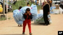 FILE - Internally displaced Iraqis carry humanitarian aid being distributed at a refugee camp in Baghdad's western neighborhood of Ghazaliyah, Sept. 16, 2015.