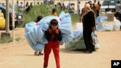 FILE - Iraqis internally displaced carry humanitarian aid being distributed at a refugee camp in Iraq.