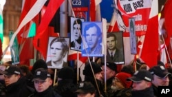 Pro-government activists hold portraits of some of the victims of the 1981 martial law crackdown and shout slogans at a passing anti-government march through downtown Warsaw on the 35th anniversary of the event, Dec. 13, 2016.