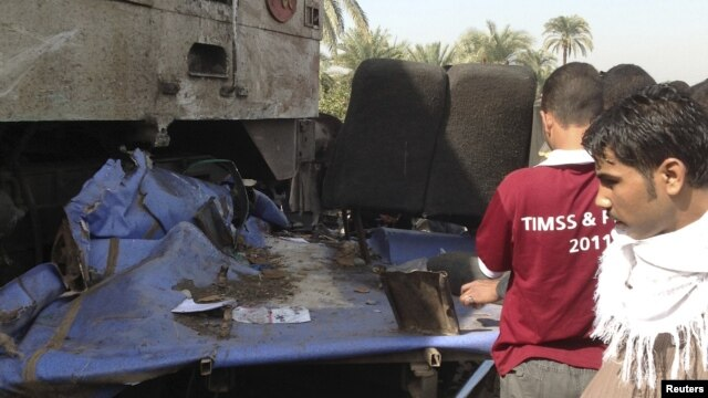 Relatives of victims look at the wreckage of a bus after a train (L), with bloodstains, crashed into it at Manflot in the southern city of Assuit, 500 km (310 miles) south of Cairo, November 17, 2012. Forty-nine people, mostly children, were killed when t
