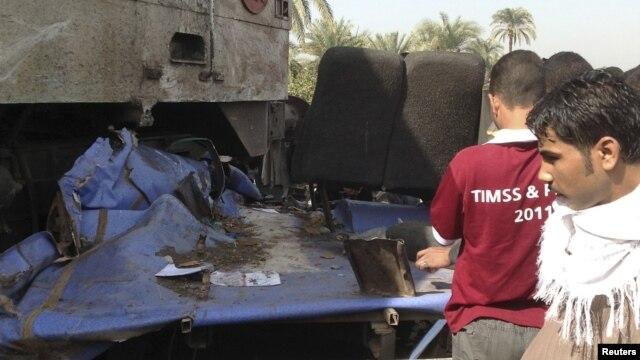 Keluarga para korban mengamati bis sekolah yang hancur setelah bertabrakan dengan kereta api di Manfalut dekat kota Assiut, 500 kilometer selatan Kairo (17/11). Lebih dari 40 anak-anak tewas dalam kecelakaan tersebut.