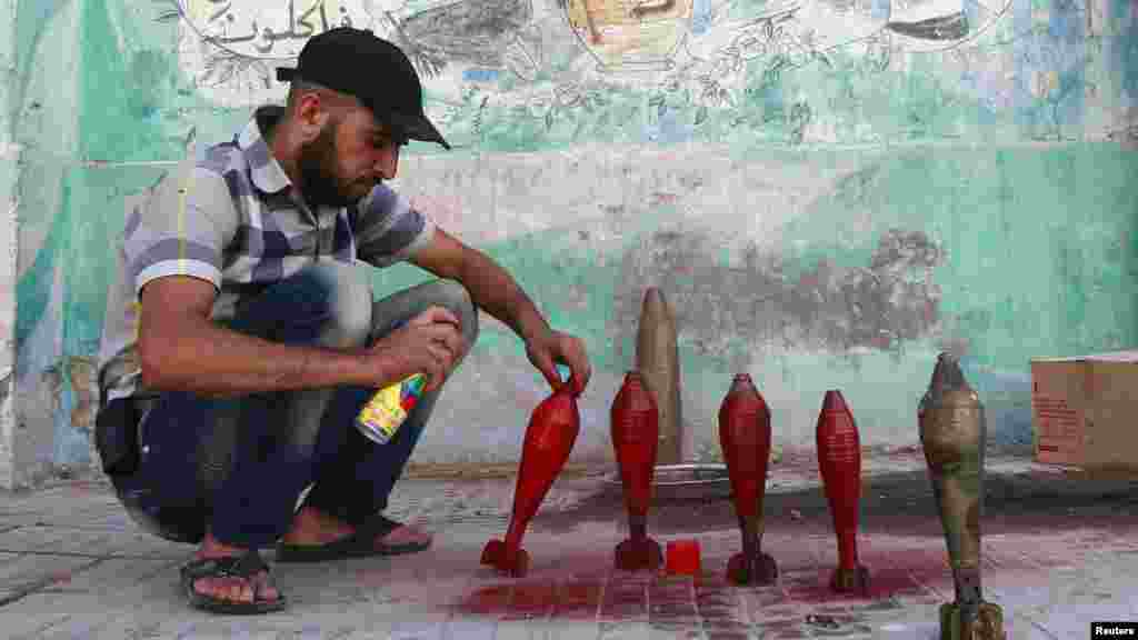 A Free Syrian Army fighter spray paints on improvised mortar shells at a weapons factory in Aleppo, Syria, Sept. 5, 2013.
