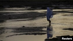 FILE - A woman walks across a river bed in Jalingo, Nigeria. REUTERS/Afolabi Sotunde