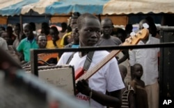 "In this photo taken Saturday, Nov. 5, 2016, a guitarist at an Ana Taban, or ""I am tired"" artists movement roadshow, plays in front of an audience in Juba, South Sudan. For many in South Sudan, the arts have become a rare haven of peace in a young country that has known little but civil war."