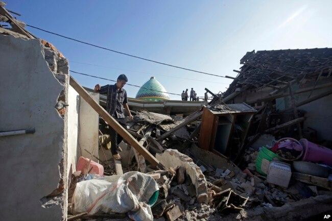 Un hombre inspecciona las ruinas de su casa destruída por un terremoto en el norte de Lambock, Indonesia, el jueves, 9 de agosto de 2018.