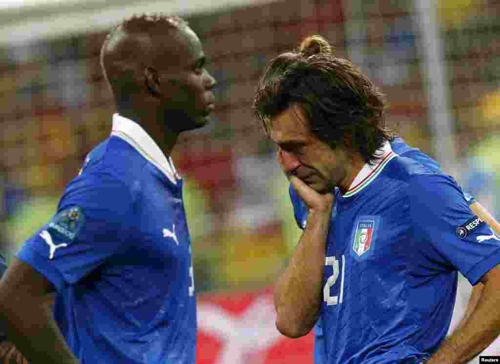 Italy's Andrea Pirlo (R) and Mario Balotelli react after losing their Euro 2012 final soccer match against Spain at the Olympic stadium in Kiev July 1, 2012.