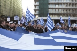 "FILE - Protesters hold a Greek flag during a rally against the use of the term ""Macedonia"" in any settlement to a dispute between Athens and Skopje over the former Yugoslav republic's name, in Athens, Greece, Feb. 4, 2018."