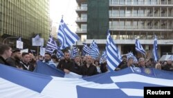 "Protesters hold a Greek flag during a rally against the use of the term ""Macedonia"" in any settlement to a dispute between Athens and Skopje over the former Yugoslav republic's name, in Athens, Greece, Feb. 4, 2018."