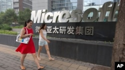 FILE - women walk past the logo for Microsoft in Beijing, China, July 31, 2014.