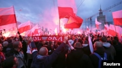 Protesters carry Polish flags and National Radical Camp flags during a rally, organized by far-right, nationalist groups, to mark 99th anniversary of Polish independence in Warsaw, Nov. 11, 2017.