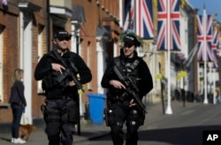 Armed police officers patrol on the streets in Windsor, England, May 17, 2018. Britain's Prince Harry and Meghan Markle will marry in Windsor on Saturday.