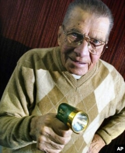 Eugene Polley, inventor of the wireless television remote control, holding his revolutionary device.