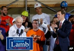 FILE - Former Vice President Joe Biden points at Conor Lamb, right, the Democratic candidate for the March 13 special election in Pennsylvania's 18th Congressional District, during a rally at the Carpenter's Training Center in Collier, Pennsylvania, March 6, 2018.