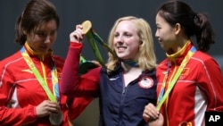 Ginny Thrasher, center, of the United States holds her gold medal for the Women's 10m Air Rifle competition during the award ceremony at the 2016 Summer Olympics in Rio de Janeiro, Brazil, Aug. 6, 2016.