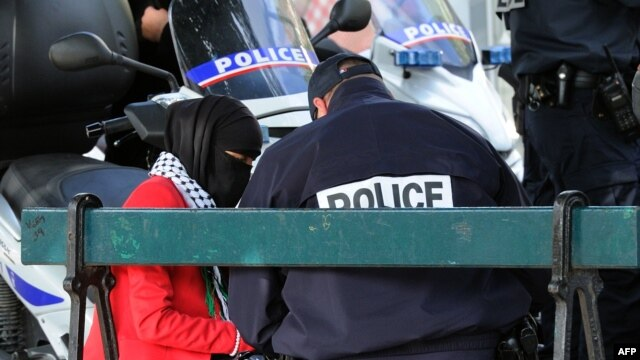 FILE - A French police officer speaks with a veiled Muslim woman during an identity check in Lille Sept. 22, 2012.