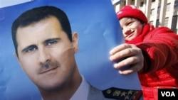 Seorang demonstran pro-pemerintah memegang potret Presiden Bashar al-Assad dalam sebuah unjuk rasa di Damaskus, Suriah (20/1).