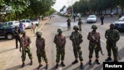 FILE - Nigerian army soldiers stand guard as they cordon off a road leading to the scene of a blast at a business district in Abuja, June 25, 2014.