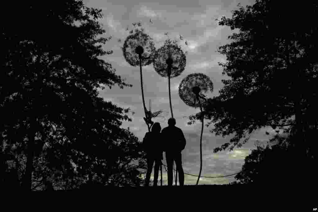 "Visitors are silhouetted as they look at ""Dandelion Sculpture"" by Amy Stoneystreet and Robin Wight at the Royal Horticultural Society Garden Wisley, in the village of Wisley, near Woking, England."