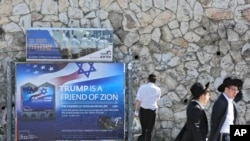 FILE - Ultra-Orthodox Jews pass by a billboard welcoming President Donald Trump ahead of his visit, in Jerusalem, May 19, 2017.