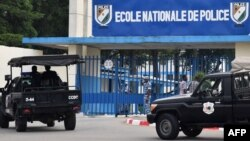 A picture taken on July 20, 2017 shows two vehicles of the Ivorian police's special forces (CCDO) outside the entrance to the National Police Academy in the Cocody district in Abidjan, where gunshots were reportedly fired on July 19.
