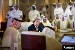 U.S. Secretary of State John Kerry (C) listens while Oman's Foreign Minister Yusuf bin Alawi (L) speaks during a meeting of foreign ministers of the Gulf Cooperation Council (GCC) in Doha Aug. 3, 2015.