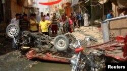 伊拉克城市迪瓦尼耶的居民2012年7月3日在该城的一家市场遭到炸弹攻击之后观看受灾现场