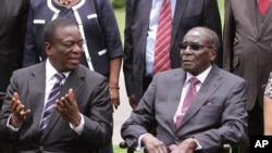 FILE - Emmerson Mnangagwa, left, vice president of Zimbabwe, chats with Zimbabwean President Robert Mugabe after the swearing-in ceremony at State House in Harare, Dec, 12, 2014.