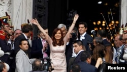FILE - Argentina's President Cristina Fernandez greets supporters as she arrives for the opening session of the 133rd legislative term of Congress in Buenos Aires, March 1, 2015.