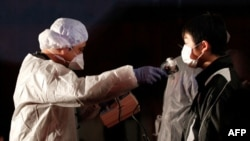 Một viên chức kiểm tra xem có dấu hiệu phóng xạ trên người một người đàn ông vừa mới di tản ra khỏi khu vực nhà máy điện hạt nhân ở Koriyama