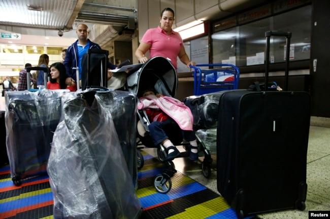 Natalie Pereira (C) se prepara para pasar por inmigración antes de mudarse a EE.UU. con su familia, después de ganar la residencia en la Lotería de Visas. Aeropuerto Maiquetía. Caracas, abril 8, de 2014.