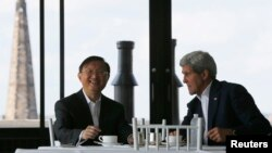 China's State Councillor Yang Jiechi, left, and U.S. Secretary of State John Kerry talk over tea during a day of meetings in Boston, Massachusetts, Oct. 18, 2014.