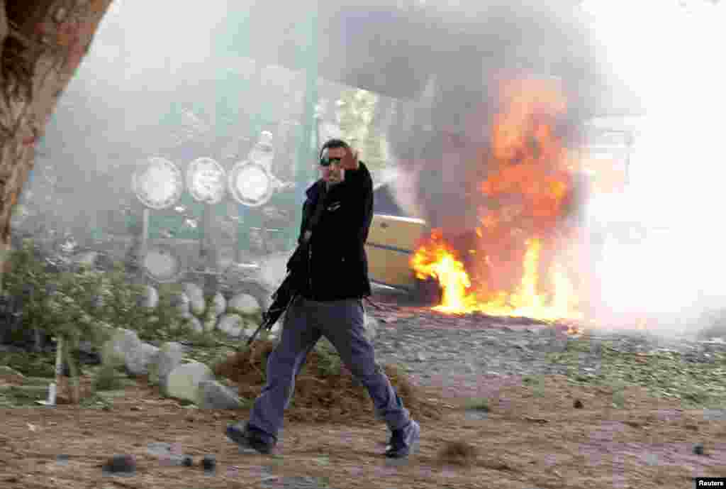 An Israeli police officer gestures in front of a burning car after a rocket fired by Palestinian militants in Gaza landed in the southern city of Ashkelon, November 18, 2012. (Reuters)