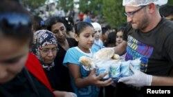 Para migran Suriah antri untuk mendapatkan pembagian makanan dari LSM lokal di kamp mereka di Edirne, Turki (foto: dok).