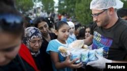 叙利亚移民在土耳其埃迪尔内附近一个高速公路旁从当地一个非营利组织那里排队领取食物。(2015年9月17日,资料图片)