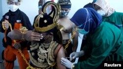 Seorang petugas kesehatan menyuntikkan vaksin Sinovac kepada seorang pria berkostum wayang, saat pemerintah melakukan vaksinasi massal untuk COVID-19, di Jawa Tengah. (Foto: Antara via Reuters)