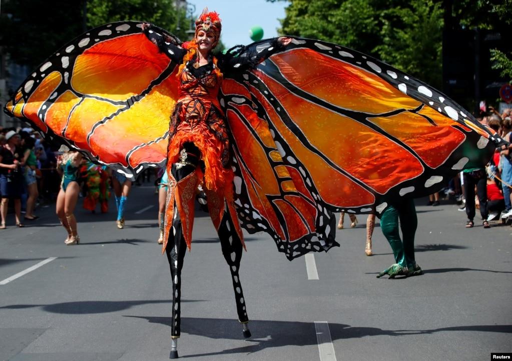Исполнитель принимает участие в ежегодном уличном параде, который является частью карнавала культур, празднующих многонациональное разнообразие города, в Берлине, Германия.