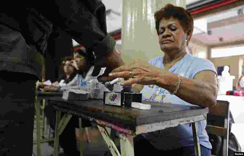 Un miembro de mesa sumerge en la tinta el dedo de un soldado luego que votó, el domingo 14 de abril en Venezuela.