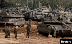 Israeli soldiers stand next to tanks and armoured personnel carriers (APC) near the border with Gaza, in southern Israel, March 26, 2019.