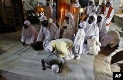 来自尼日利亚的基督徒朝圣者在伯利恒的圣诞洞祷告。(2012年12月24日)