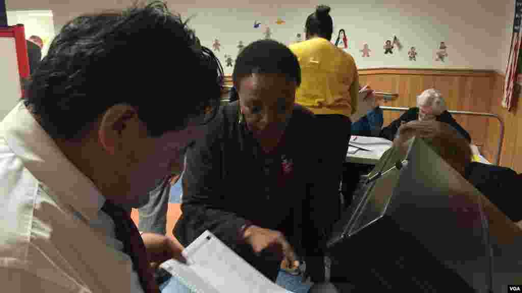Des électeurs de Mamaroneck, ville américaine située dans le comté Westchester, dans l'Etat de New York, viennent voter à la dernière minute dans les primaires peu avant la fermeture du bureau de vote à 21hrs, le mardi 19 avril 2016 (VOA/Jacques Aristide)
