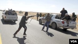 Seorang pejuang pemberontak di Ras Lanuf, berlari menuju sebuah mobil dengan senapannya, Minggu (6/3).