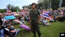 A Thai soldier stands as anti-government protesters sit at the Royal Thai Army compound in Bangkok, Thailand, Friday, Nov. 29, 2013.