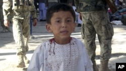 An Afghan boy, who lost his father in a suicide attack, walks around a hospital in a daze in Maymana, Faryab province north west of Kabul, Afghanistan, October 26, 2012.