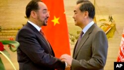 FILE - Afghan Foreign Minister Salahuddin Rabbani, left, and Chinese Foreign Minister Wang Yi, right, shake hands at the end of a joint press conference at the Ministry of Foreign Affairs in Beijing, Jan. 26, 2016.