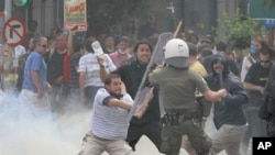 Greek protester uses a baton to hit a riot police officer during clashes in Athens' main Syntagma square, June 15, 2011