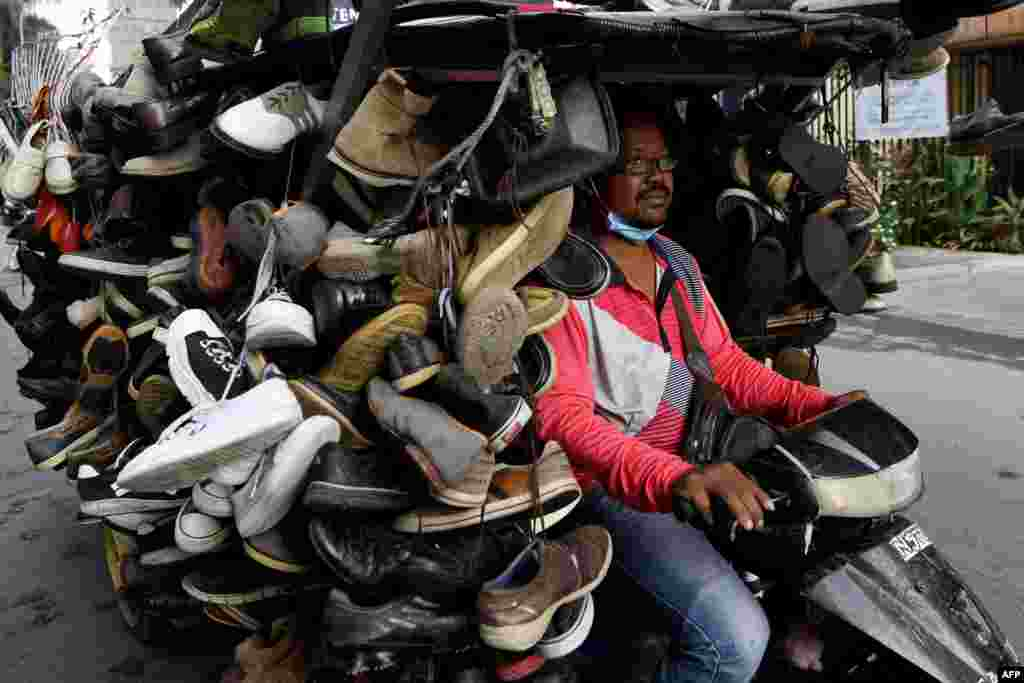 A man rides a motorcart loaded with secondhand shoes for sale on a street in Phnom Penh, Cambodia.