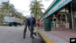 """FILE - Miami-Dade mosquito-control inspector Yasser """"Jazz"""" Compagines sprays a chemical mist into a storm drain, Aug. 23, 2016, in Miami Beach, Fla. The spread of the Zika virus has been limited in Florida thanks to aggressive mosquito control."""