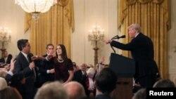 当唐纳德·特朗普总统指着有线电视新闻网记者吉姆·阿科斯塔时,一名白宫助手试图接过麦克风。