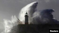Một ngọn sóng khổng lồ chụp lên ngọn hải đăng, nơi một cậu bé 14 tuổi đã bị cuốn trôi ra biển ở Newhaven, Đông Nam nước Anh ngày 28 tháng 10, 2013.